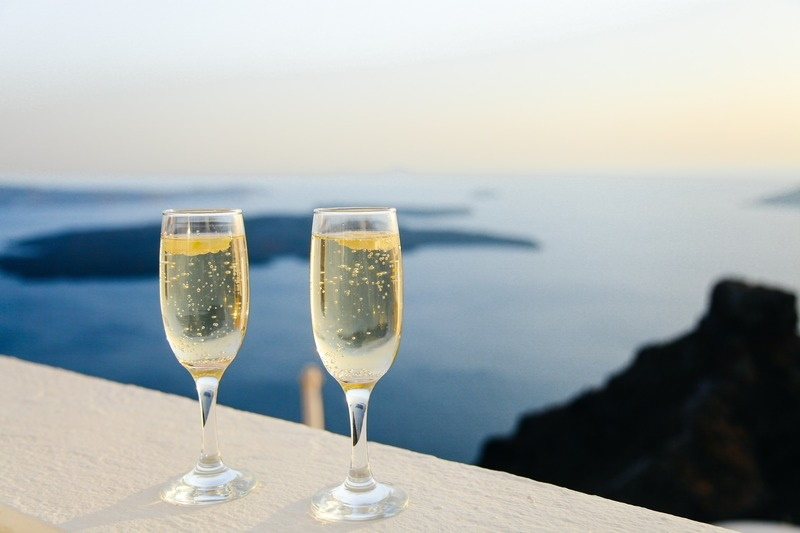 Glasses of sparkling wine on a ledge overlooking the ocean.