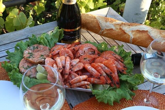Platter of shrimp on a table with wine