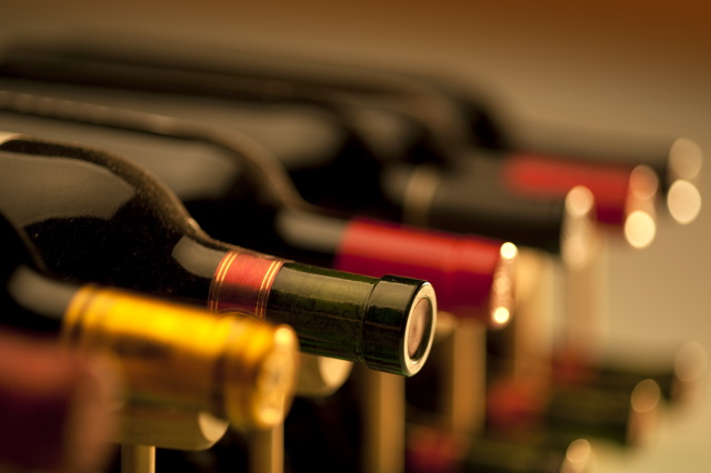 Row of bottles on a wine rack close-up
