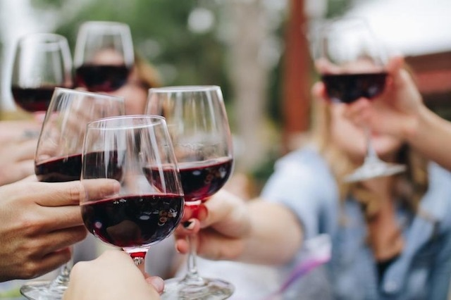 Closeup of people toasting glasses of red wine
