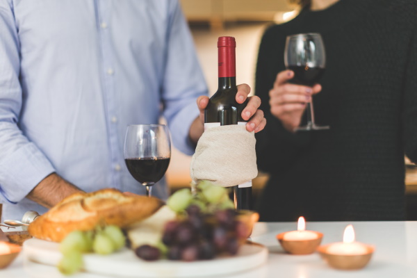 Two people in front of a table with a bottle and glasses of red wine