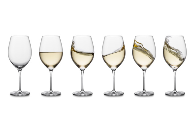 Glasses of white wine in a row on white background with various swirling patterns
