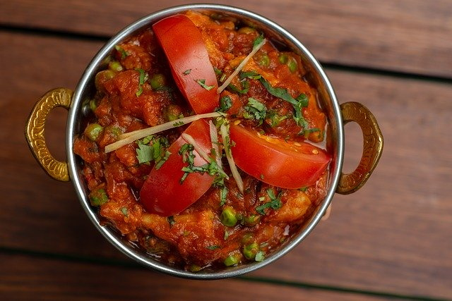 Indian dish of chicken thighs garnished with tomatoes