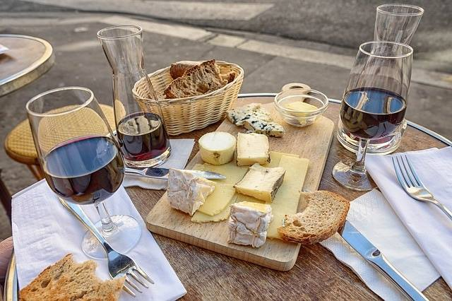 Glasses of red wine surrounded by cheese platter and a basket of bread