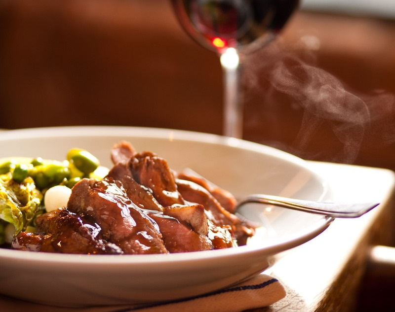 Dish of lamb with a glass of red wine in the background