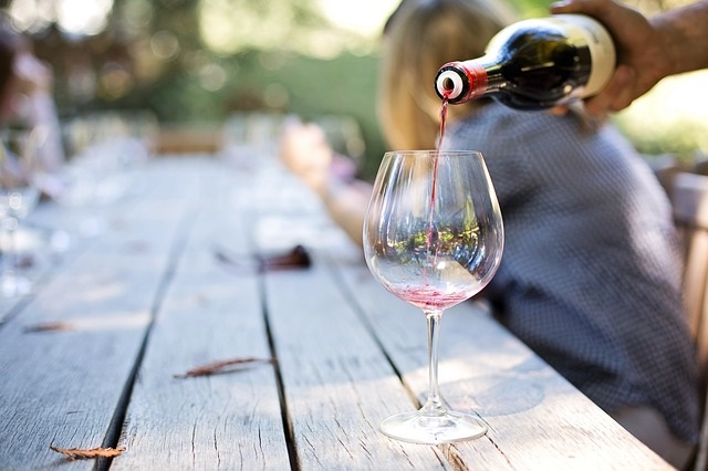 Pouring red wine into a glass at an outdoor table