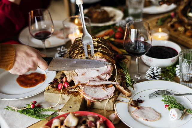 Roast pork loin being carved on a table with glasses of red wine.